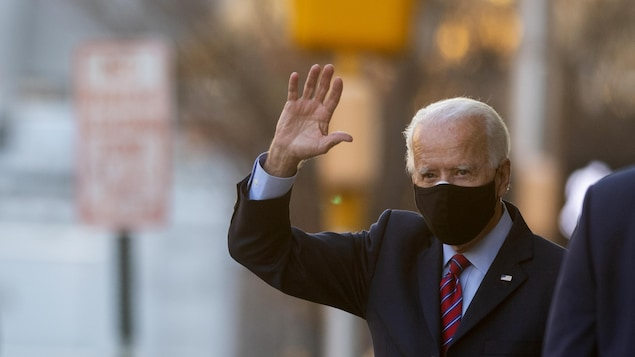 Joe Biden portant un masque, fait un salut de la main.