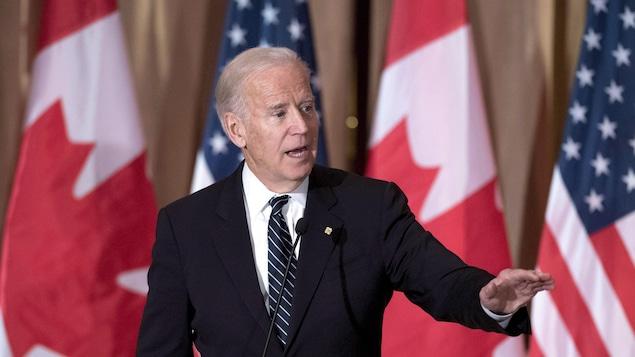Le vice-président américain Joe Biden devant des drapeaux canadiens et américains