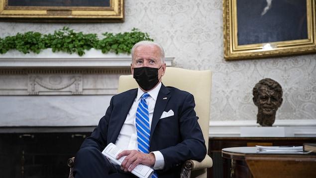 Joe Biden est assis sur une chaise dans le bureau ovale à la Maison-Blanche.