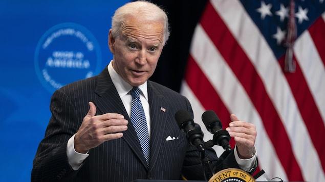 Joe Biden devant un lutrin, près d'un drapeau des États-Unis.