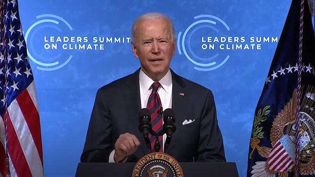 Joe Biden, en veston et cravate, parle dans deux micros, devant d'immenses drapeaux américains.