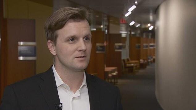 Le conseiller Joe Cressy en entrevue avec CBC, dans un couloir, il porte une chemise blanche et un veston noir, il a les cheveux châtains clairs
