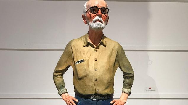 Une scupture représentant l'artiste Joe Fafard, debout, le téléphone dépassant de la poche de sa chemise.