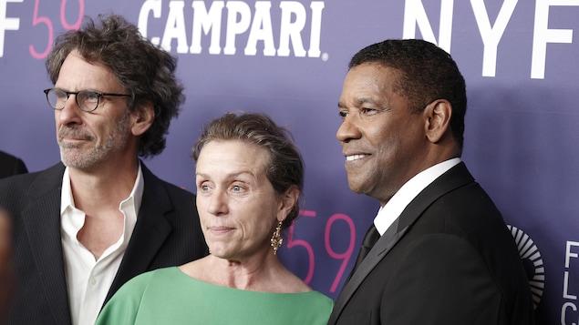 Deux hommes et une femme posent pour les caméras lors de la première d'un film à New York.