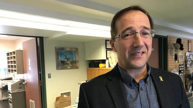 Un homme regarde la caméra dans un bureau.