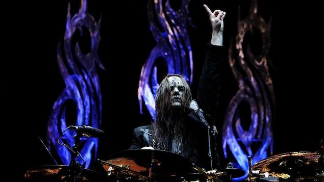 Joey Jordison est assis derrière sa batterie sur scène et porte un masque d'horreur. Derrière lui, on aperçoit le logo du groupe Slipknot.