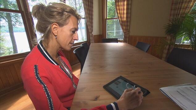 Johanne Lavoie regarde une tablette.