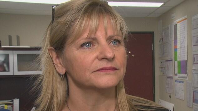 La femme est debout devant la caméra de Radio-Canada dans un bureau du CISSS.