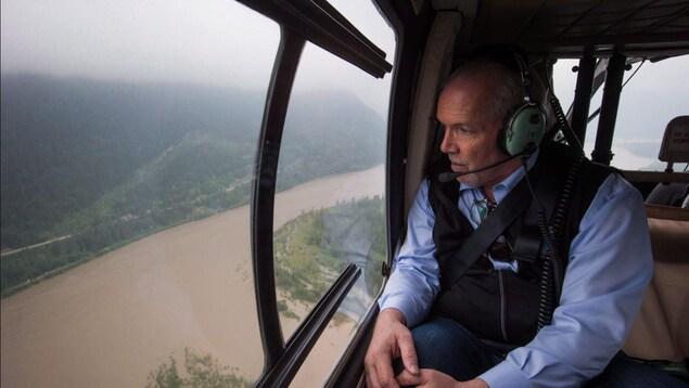 Le premier ministre John Horgan est dans un hélicoptère et regarde par la fenêtre le fleuve Fraser qui déborde de son lit.