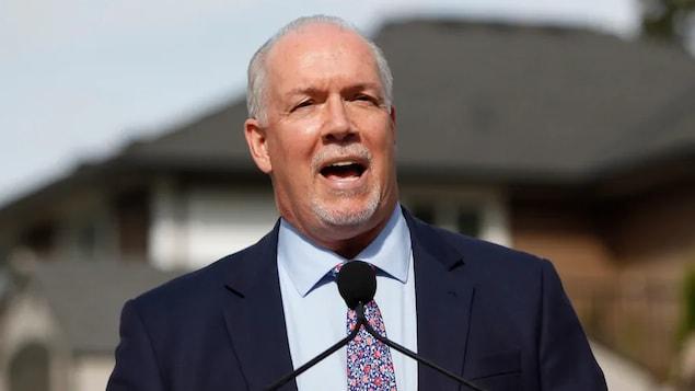 Le chef du NPD, John Horgan, est debout devant un micro lors de la campagne électorale.