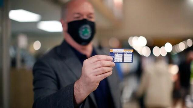 John Horgan montrant une carte indiquant qu'il a été vacciné contre la COVID-19.