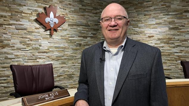 Un homme souriant en veston et portant des lunettes se tient devant un bureau et un logo d'une fleur de lys argent à l'intérieur d'une feuille d'érable rouge.