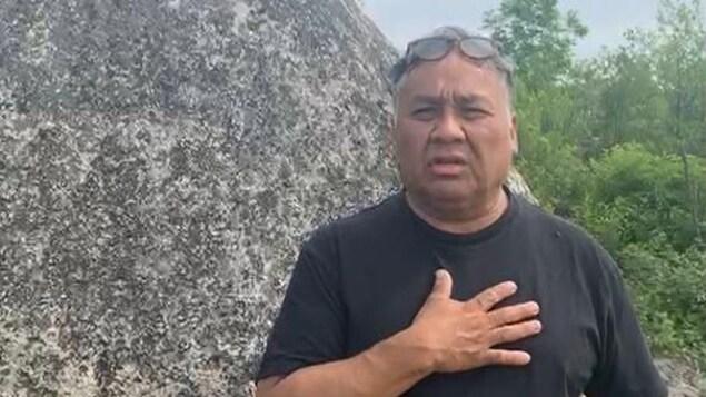 John Mowatt sur le site Apitipik près d'une grosse roche.