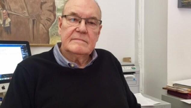 Un portrait du coordonnateur de la Coalition torontoise sur la responsabilisation de la police, John Sewel devant son bureau. Il porte des lunettes et est âgé de 77 ans.