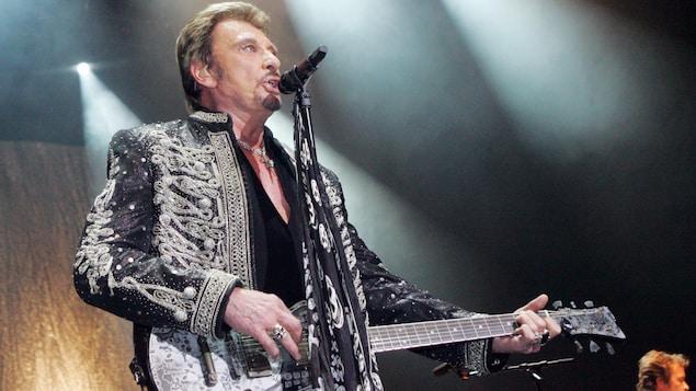 Johnny Hallyday, avec sa guitare, offre une prestation musicale à l'Olympia de Paris en décembre 2006.