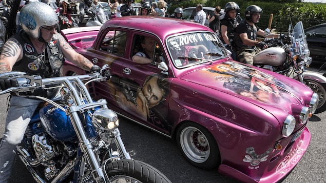 Des motards en convoi accompagne une voiture Renault Dauphine rose peinte avec des portraits du chanteur Johnny Hallyday sur une route.