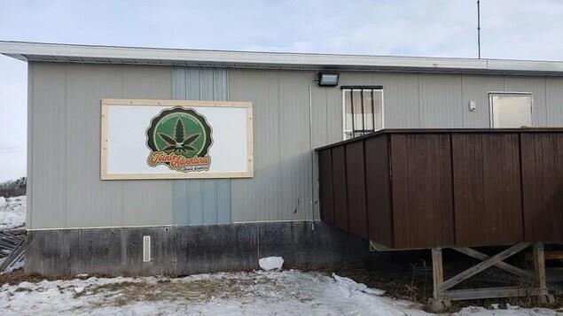 Un bâtiment rectangulaire sur lequel une pancarte montre une feuille de marijuana et le nom de l'entrepriseJoint Adventures