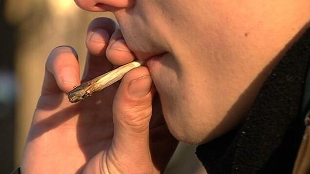 Un consommateur fume un joint de marijuana.