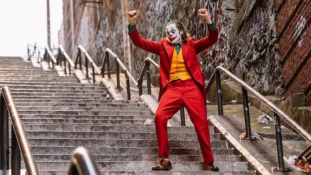 Un homme déguisé en clown est debout dans un escalier, les mains levées.