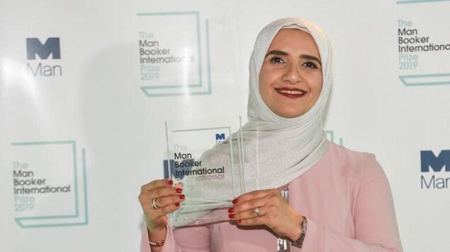 Jokha Alharthi souriant en tenant son prix (une plaque en vitre) entre ses mains.