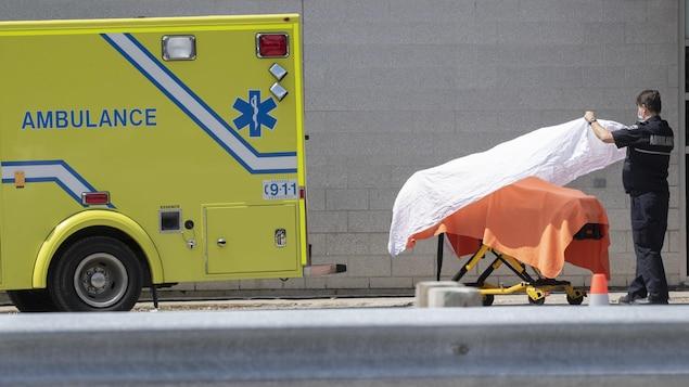 Un ambulancier dépose un drap blanc sur une civière.