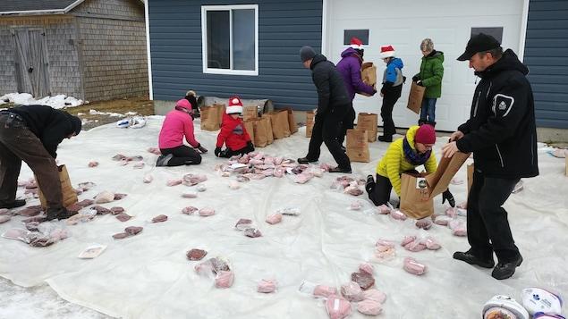 Dens dans une entrée de garage placent des pièces de viande dans des sacs.