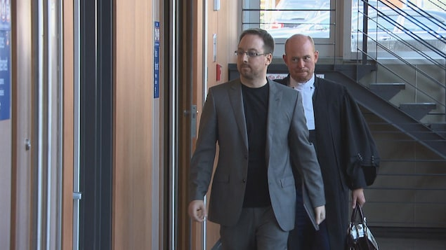 Jonathan Bettez et son avocat dans le couloir.