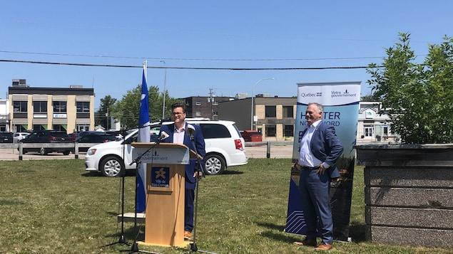Yves Montigny et Jonathan Julien sont tous les deux devant un podium avec un drapeau du Québec derrière eux, ils se trouvent sur un espace vague vert.