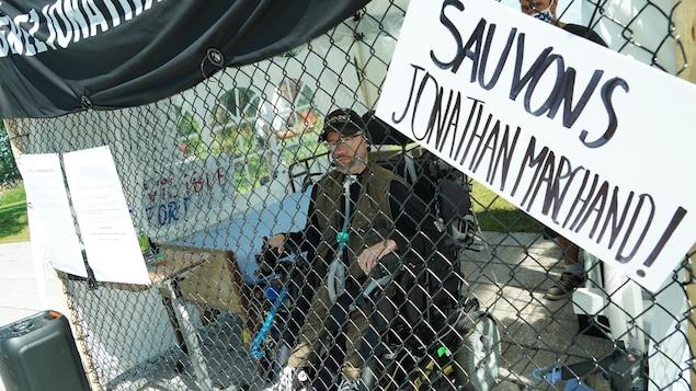 Jonathan Marchand manifeste, dans sa cage, devant l'Assemblée nationale.