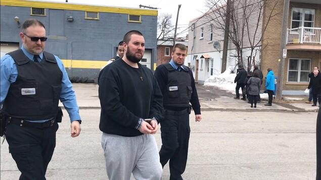 Des policiers escortent Jonathan Rochette, menottes aux poignets, vers l'endroit où lui et ses présumés complices auraient dissimulé de la drogue