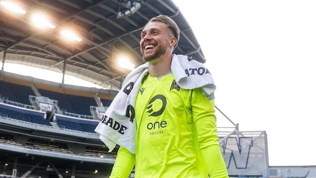 Un gardien de but souriant dans un stade.