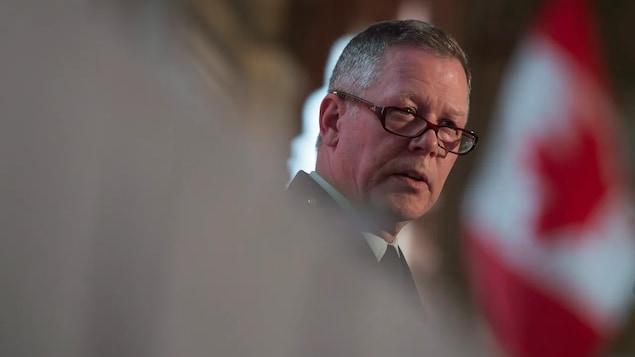 M. Vance, lunettes sur le bout du nez, devant un drapeau du Canada.