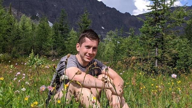 Photo du jeune Jordan Naterer assis dans l'herbe devant des montagnes rocheuses.