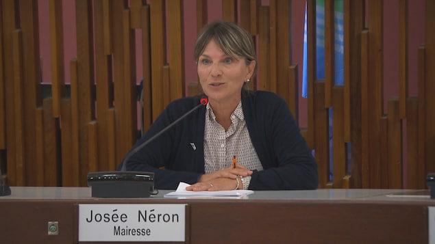 Une femme est à la table du conseil municipal et parle à un micro.