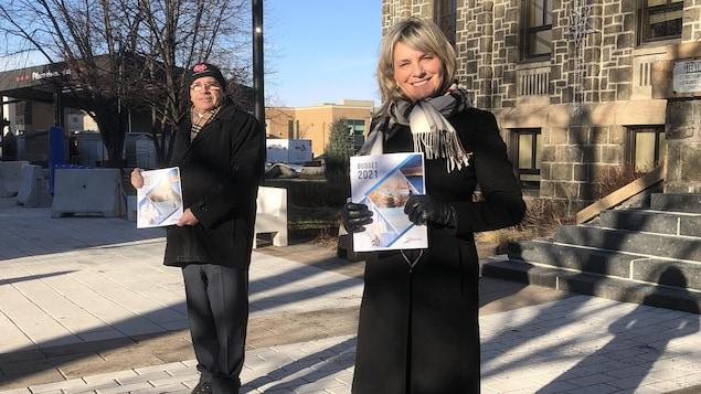 Michel Potvin et Josée Néron tiennent chacun une copie du budget devant l'hôtel de ville.