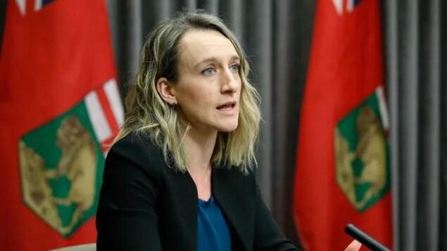 Dre Joss Reimer lors d'une confrérence de presse. Elle est devant des drapeaux du Manitoba et un rideau gris.