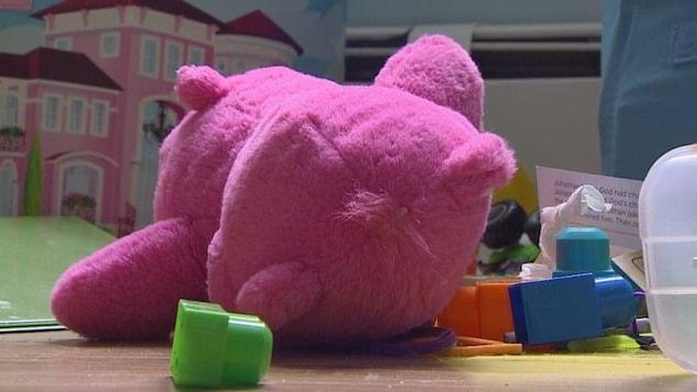Un ourson en peluche rose sur un plancher.