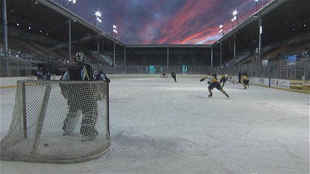Des joueurs des Cataractes de Shawinigan s'entraînent au coucher de soleil sur la patinoire extérieure à Saint-Tite.