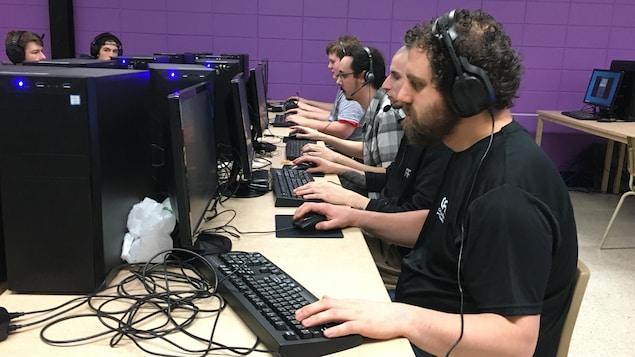 Des amateurs de jeux vidéo s'amusent en pianotant sur des claviers.