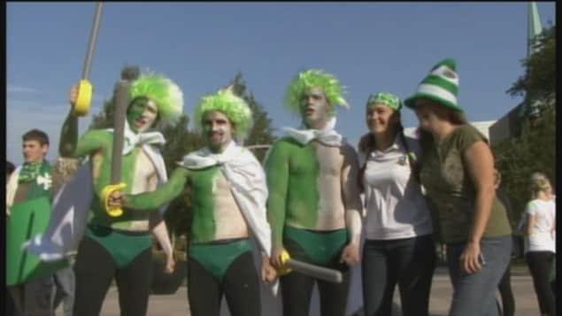 Des jeunes hommes avec des perruques vertes et blanches et le torse peint en vert et blanc, avec de jeunes femmes qui portent les couleurs des Franco-Ontariens.