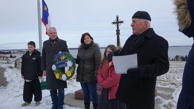 Un homme fait un discours à côté de deux adultes et deux enfants. Au fond, le drapeau acadien et une croix. En arrière-plan, le port de Charlottetown.