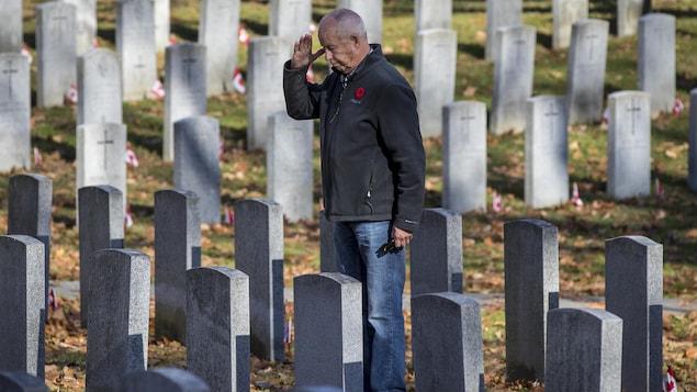 Un homme se recueille, seul, devant la tombe d'un militaire mort au combat.