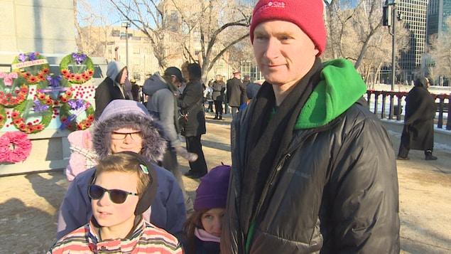 Un homme avec trois enfants devant le cénotaphe de la place Victoria, à Regina.