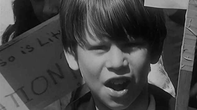 Gros plan sur le visage d'une petit garçon expressif qui tient une pancarte.