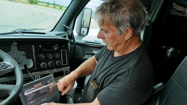 Un homme utilise un carnet de bord électronique à bord de son camion.