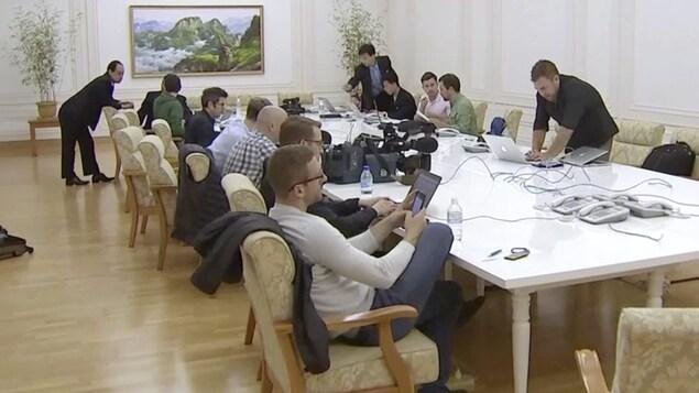 Des journalistes sont assis autour d'une table avec des ordinateurs portatifs et des téléphones cellulaires. Des Nord-Coréens sont debout autour de la table. .