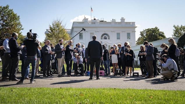 Le politicien, de dos, parlent aux micros de dizaines de journalistes.