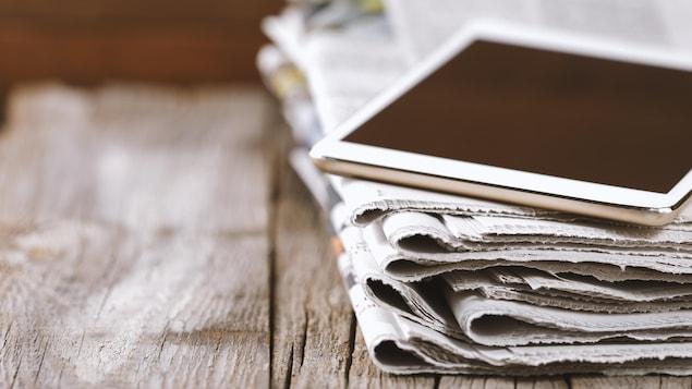 Une pile de journaux et une tablette.