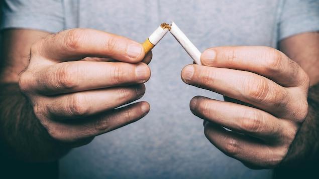 Des mains masculines brisent une cigarette.
