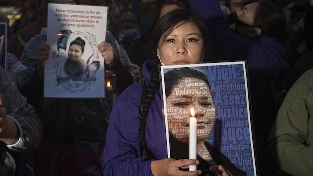 Une femme tient le portrait de Joyce Echaquan et une chandelle.